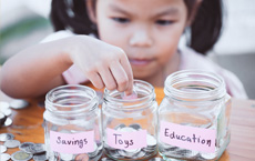little girl counting coins into savings jars with different labels